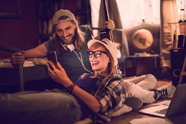 Paar in Wohnzimmer lacht mit Handy