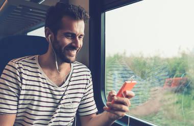 Mann im Zug sieht auf Smartphone